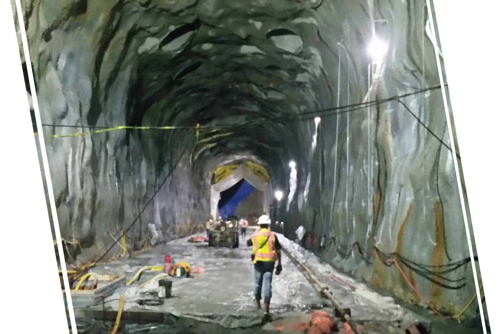 A long underground tunnel with a worker walking down it