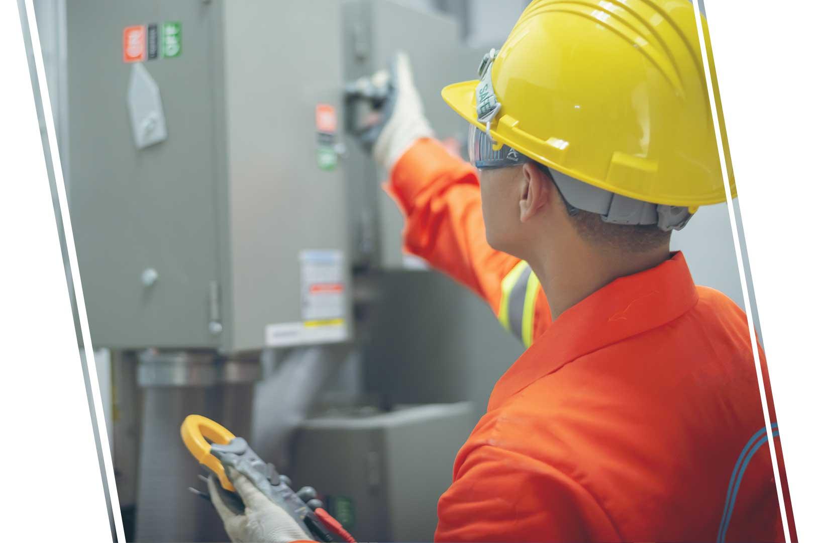 Worker wearing hardhat checking an electrical box